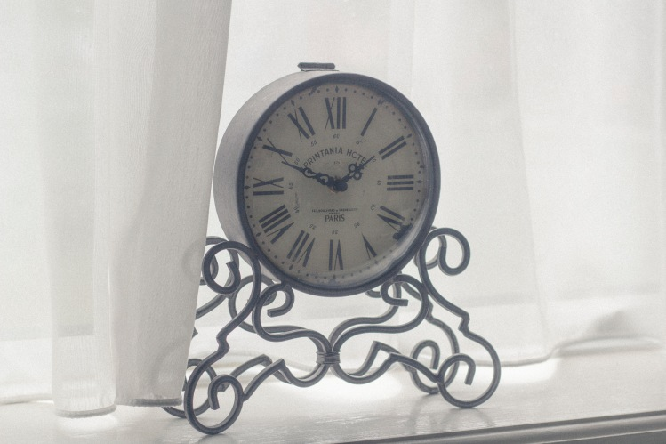 Metal clock in window_Tomasz Bazylinski_Stocksnap